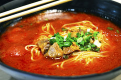 在大碗的健康中国蕃茄牛肉汤面有一个对的筷子 免版税库存照片