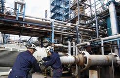在大精炼厂产业里面的油和煤气工作者 免版税图库摄影