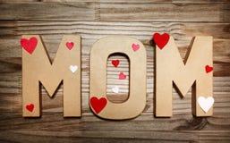 在大纸板信件的妈妈文本与心形的装饰 免版税库存图片