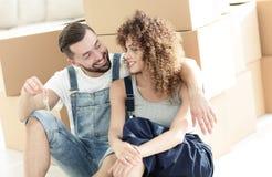 在大纸板箱背景的微笑的夫妇  库存图片