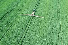 在大绿色的鸟瞰图农业机械喷洒的化学制品 库存图片