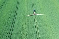 在大绿色的鸟瞰图农业机械喷洒的化学制品 免版税库存照片