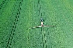 在大绿色的鸟瞰图农业机械喷洒的化学制品 图库摄影
