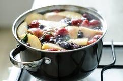 在大罐的乌克兰莓果和苹果kompot在煤气炉,新鲜水果饮料 免版税库存图片