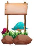 在大蘑菇和岩石附近的一块空的木牌 库存图片