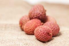 在大袋亚麻布布料的被堆积的lychee果子 库存图片
