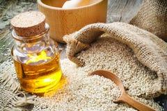 在大袋和瓶的芝麻籽在土气桌上的油 免版税图库摄影