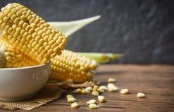 在大袋和甜玉米种子土气木桌背景的新鲜的玉米 免版税图库摄影
