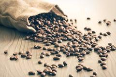 在大袋外面的咖啡豆溢出 免版税图库摄影