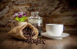 在大袋的咖啡在木桌上有老墙壁背景 例证百合红色样式葡萄酒 免版税库存照片