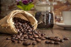 在大袋的咖啡种子在与自然光的木桌上 库存图片