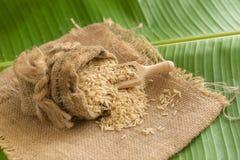 在大袋的糙米在香蕉叶子 免版税库存图片