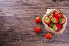在大袋的草莓在与空间的木桌上措辞的 库存照片