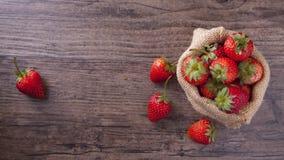 在大袋的草莓在木桌上 图库摄影