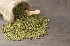 在大袋的绿豆有在木背景的木匙子的 免版税图库摄影