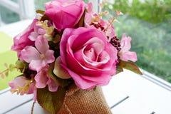 在大袋袋子的假桃红色玫瑰在窗口机智附近的白色木桌上 库存图片