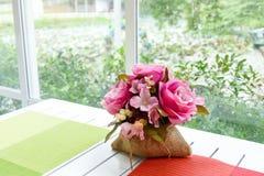 在大袋袋子的假桃红色玫瑰在窗口机智附近的白色木桌上 免版税库存照片