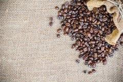 在大袋袋子的咖啡豆在粗麻布背景 库存照片