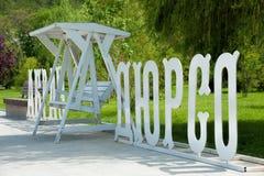 在大词纪念碑之间的白色长凳在Abrau杜尔索,新罗西斯克,俄罗斯的堤防 免版税图库摄影