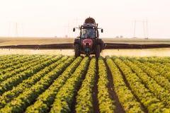 在大豆领域的拖拉机喷洒的杀虫剂与在spr的喷雾器 免版税图库摄影