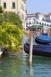 在大运河的看法有在港口和Rialto Bridge Ponte de Rialto,威尼斯,意大利的长平底船的 免版税库存图片