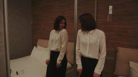 在大镜子附近的妇女在舒适微弱光线卧室 影视素材