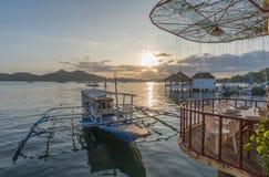 在大阳台咖啡馆的传统小船在日落视图的Coron镇 免版税库存照片