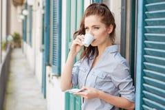 在大阳台的妇女饮用的咖啡在一个早晨 库存照片