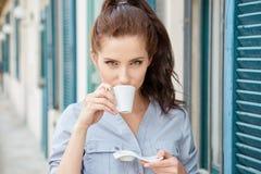 在大阳台的妇女饮用的咖啡在一个早晨 库存图片
