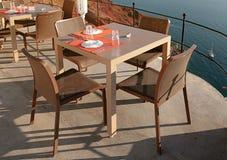 在大阳台的室外咖啡馆在沿海,圣托里尼 免版税图库摄影