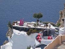 在大阳台的惊人的室外就座在充满活力的蓝色爱琴海,圣托里尼海岛的破火山口 免版税库存图片