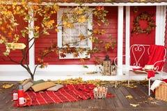 在大阳台的秋天野餐 红色格子花呢披肩、篮子用苹果和热水瓶有热的饮料的 乡下房子游廊  免版税图库摄影