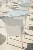 在大阳台的空的咖啡馆在一个夏日,没有客人、白色椅子和桌 免版税库存照片