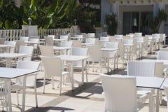 在大阳台的空的咖啡馆在一个夏日,没有客人、白色椅子和桌 库存照片