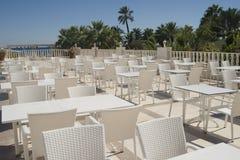 在大阳台的空的咖啡馆在一个夏日,没有客人、白色椅子和桌 库存图片