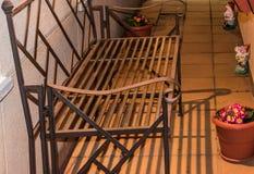 在大阳台的空的金属箔长凳 免版税库存照片