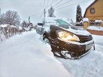 在大随风飘飞的雪困住的黑斜背式的汽车汽车 冬天运输问题 冻汽车 免版税图库摄影