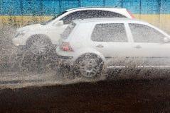 在大雨期间,从汽车下面轮子飞溅 库存图片
