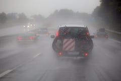 在大雨的汽车通行 免版税库存图片