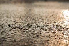 在大雨软的焦点以后的湿沥青边路背景 免版税库存图片