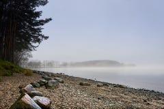在大雾后和海岛掩藏的湖边岸 免版税库存图片