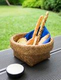 在大面包在篮子的食物快餐上添面包与蓝色餐巾和白汁 库存图片