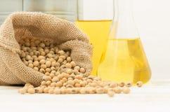 在大麻大袋袋子的大豆与在实验室玻璃设定的油在木桌上 库存照片