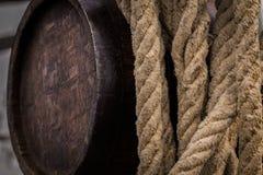 在大麻绳索旁边的老被风化的liquer桶 免版税库存图片
