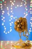 在大玻璃的发光的圣诞节装饰品在蓝色背景 图库摄影