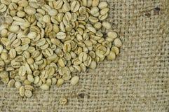 在大麻背景的未经焙烧的咖啡豆 库存照片