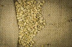 在大麻背景的未经焙烧的咖啡豆 库存图片