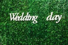 在大绿色墙壁上的白色题字婚礼之日 免版税库存照片