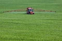 在大绿色领域的拖拉机喷洒的杀虫剂 免版税库存图片