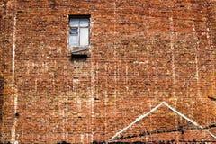 在天中午光的高明的砖墙纹理背景与残破的窗口 库存图片